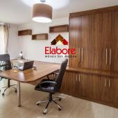 Mesa em mdf com pé cromado, armário sob medida em mdf e nichos decorativos.