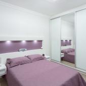 Quarto sob medida. Cabeceira com lâmpadas de led, papel de parede lilás, criados com frentes de gaveta em vidro pintado